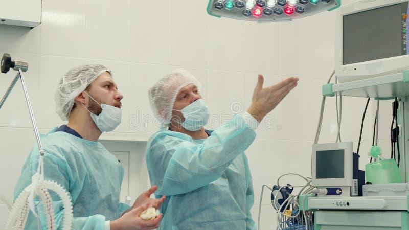 Os cirurgiões discutem algo no monitor fotos de stock royalty free