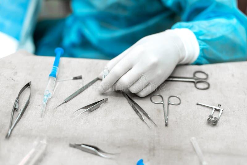 Os cirurgiões entregam a tomada de tesouras, de fórceps e de instrumentos cirúrgicos na tabela para a operação que executa o trab imagem de stock