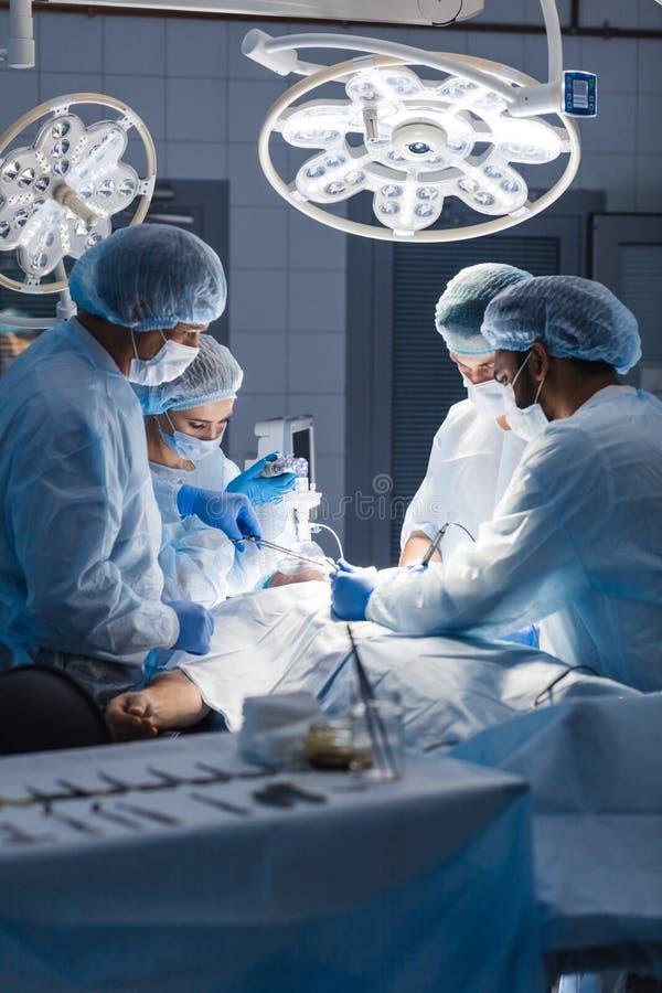 Os cirurgiões executam uma operação complexa para salvar uma vida humana no hospital foto de stock