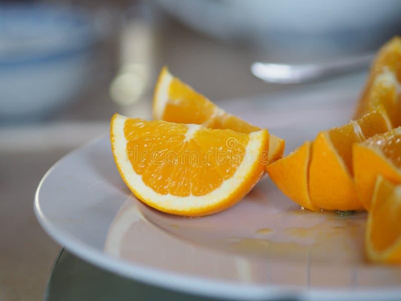 Os citrinos alaranjados têm uma fatia do gosto do agridoce no prato branco foto de stock