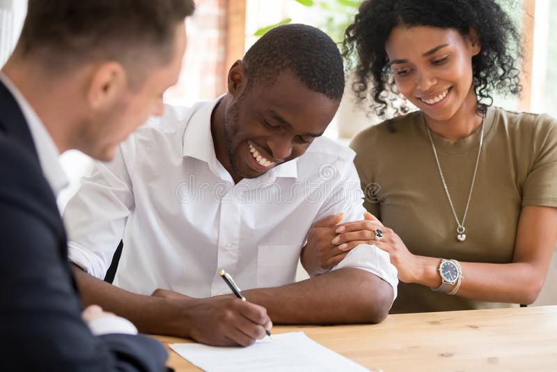 Os clientes africanos felizes dos pares da família assinam o contrato de seguro do empréstimo hipotecário fotos de stock