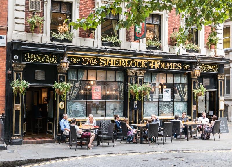 Os clientes bebem a cerveja em tabelas fora da barra de Sherlock Holmes em Londres imagens de stock royalty free