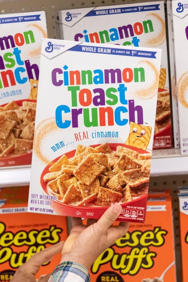 Os clientes entregam guardar um pacote do trigo do tipo do general MIlls Cinnamon Toast Crunch e do cereal do arroz fotos de stock royalty free