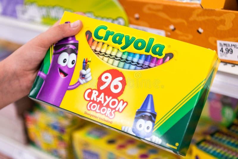 Os clientes entregam guardar uma caixa de farelos de Crayola 96 cores do pastel imagem de stock