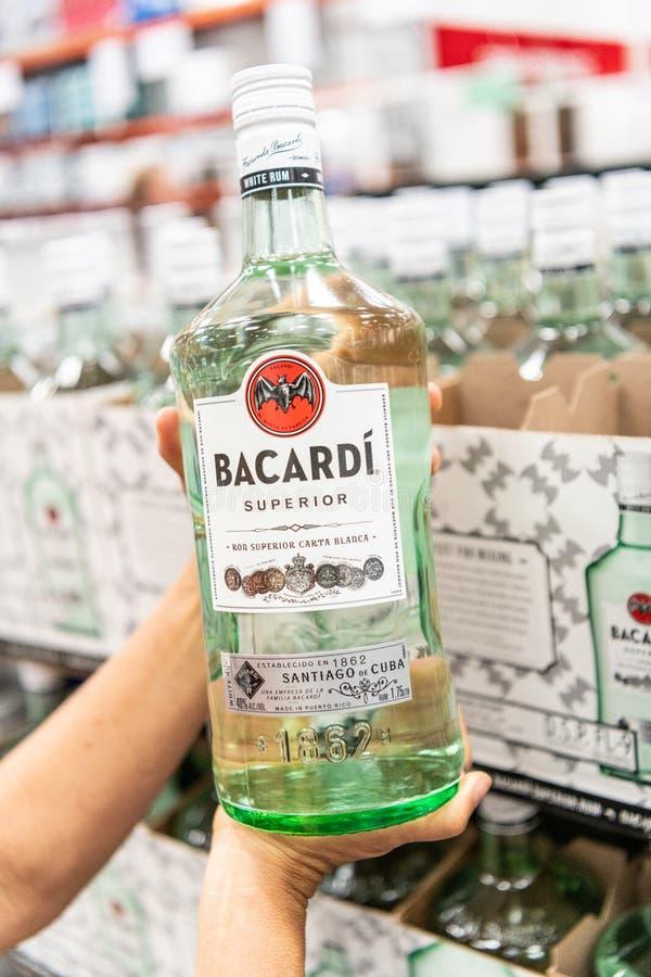 Os clientes entregam guardar uma garrafa de Bacardi Carta Blanca Superior Brand White Rum foto de stock