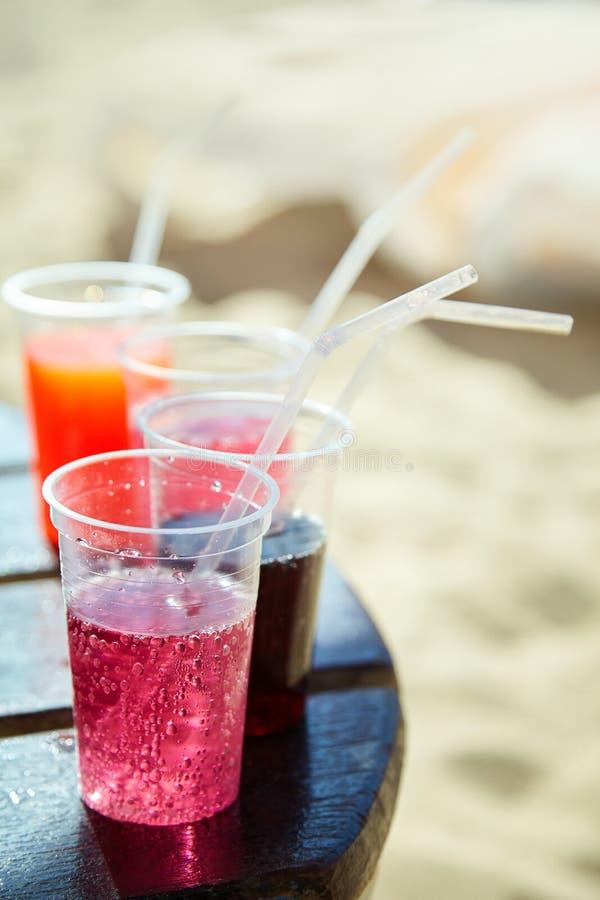 Os cocktail da praia no plástico levam embora vidros fotografia de stock royalty free