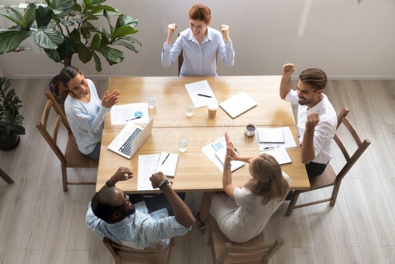 Os colegas de trabalho multi-?tnicos felizes da vista acima superior gritam, aplaudem, comemorando a vit?ria fotos de stock