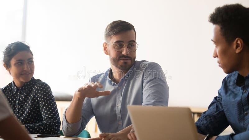 Os colegas diversos falam discutindo ideias durante o encontro no escrit?rio fotografia de stock