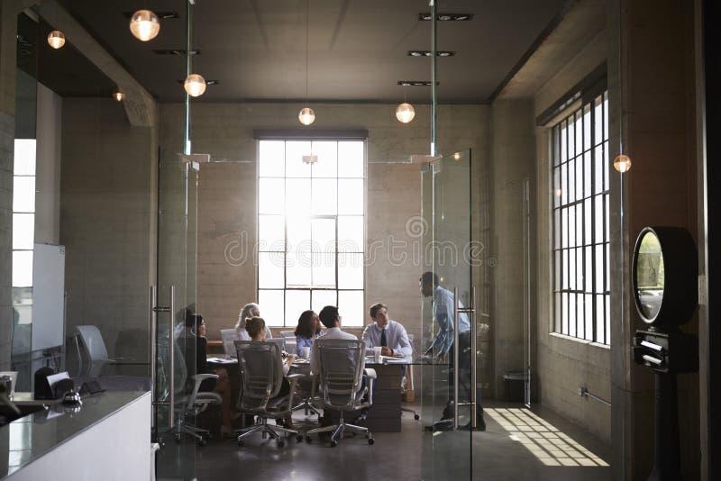Os colegas do negócio em uma reunião em um vidro muraram a sala de reuniões fotos de stock royalty free