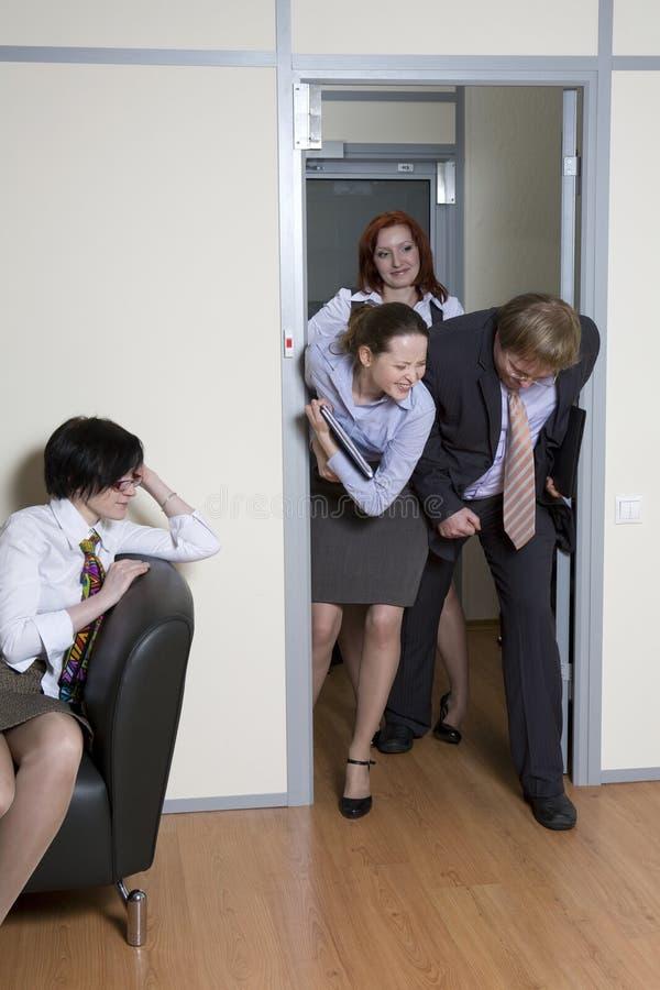 Os colegas esforçam-se nas portas para a possibilidade sejam primeiros dentro imagem de stock
