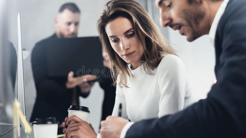Os colegas estão procurando uma solução do negócio durante o processo do trabalho no escritório ensolarado Executivos que encontr imagem de stock royalty free