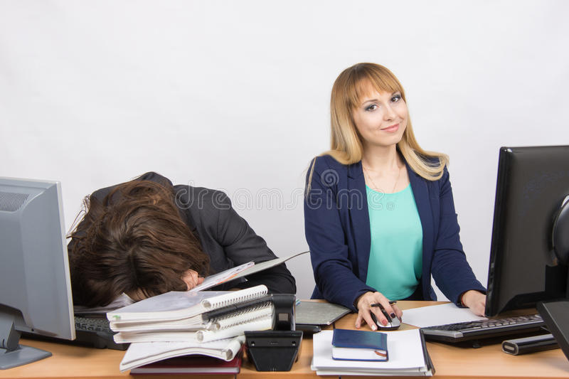 Os colegas fêmeas no escritório, um tiveram adormecido caído em uma pilha dos dobradores, os outros trabalhos no computador e olh fotos de stock