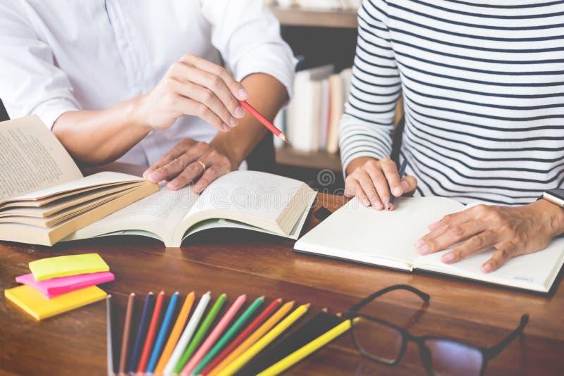 Os colegas novos dos estudantes ajudam o manual de instruções alcançando do amigo e tutoria da aprendizagem em uma biblioteca, em foto de stock