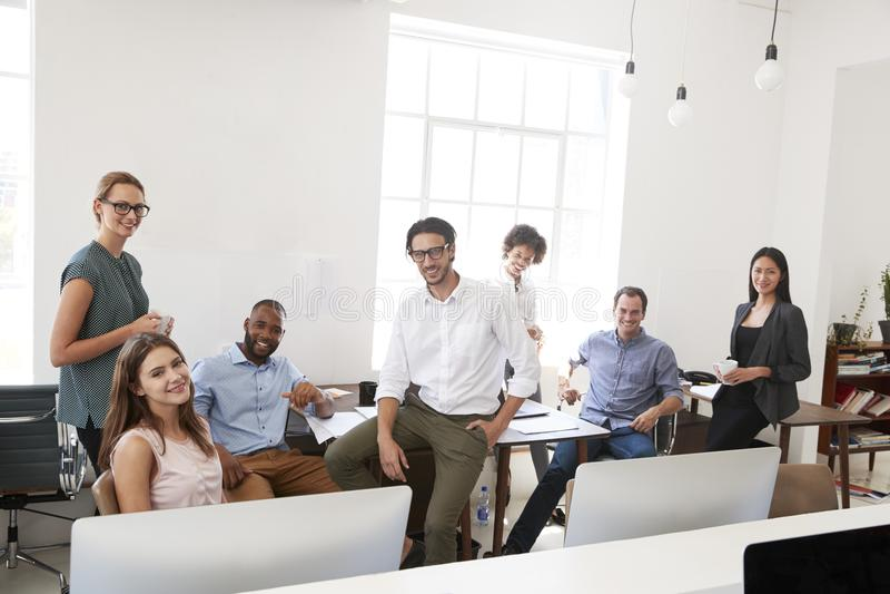 Os colegas relaxado do negócio em seu escritório sorriem à câmera fotografia de stock royalty free