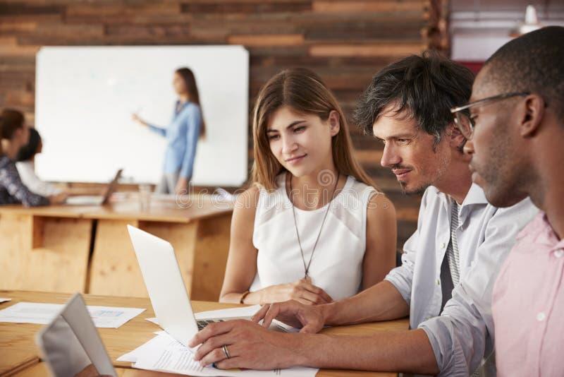 Os colegas trabalham junto no laptop em um escritório ocupado imagem de stock
