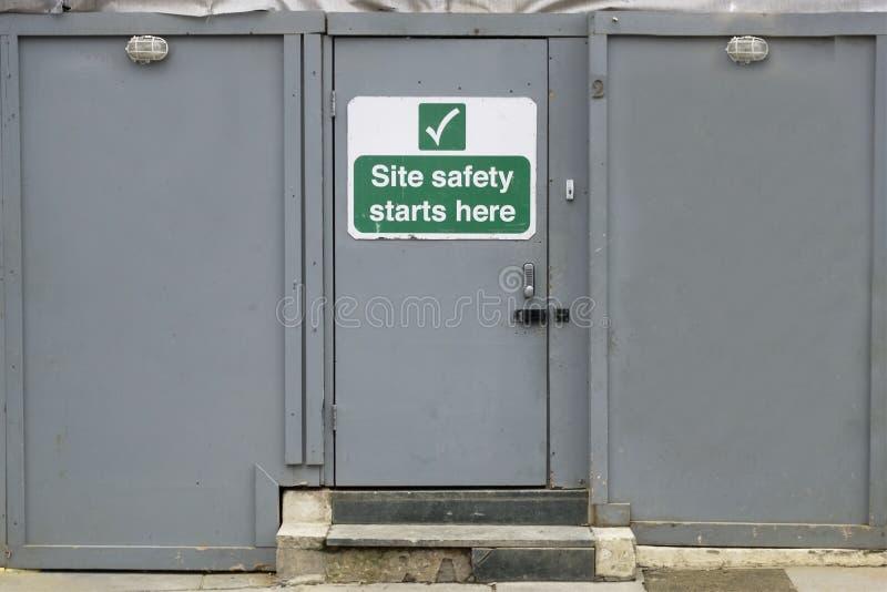 Os começos da segurança do local aqui pensam o sinal seguro da construção foto de stock