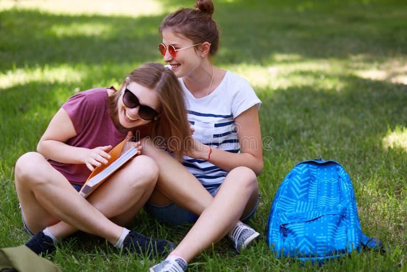 Os companheiros fêmeas engraçados têm o divertimento junto, dizem anedotas cômicas ou as estórias boas, descansam após classes na imagem de stock