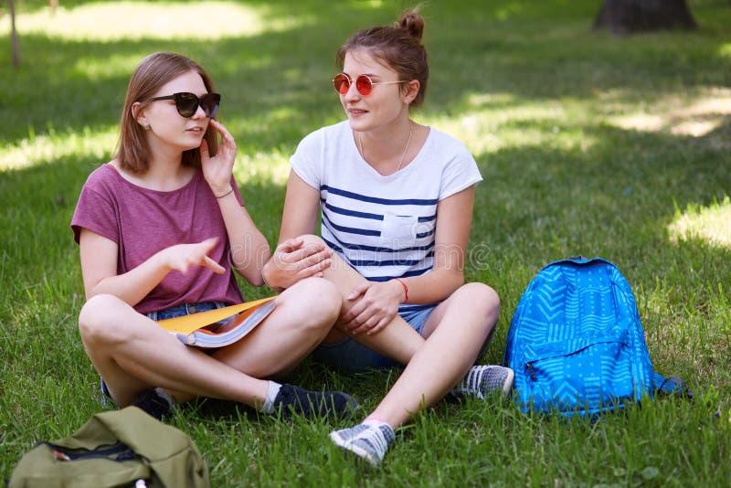 Os companheiros fêmeas positivos de vista amigáveis falam um com o otro, gesticulam com mãos, mantêm os pés cruzados, descansam n fotografia de stock