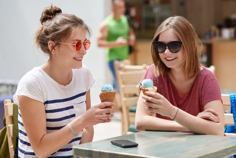 Os companheiros fêmeas positivos têm expressões alegres quando o recreat no bar junto, comer o gelado, veste óculos de sol, comun imagem de stock royalty free