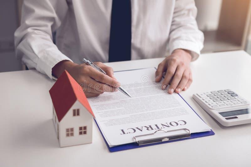 Os compradores de casa novos estão assinando um contrato de compra da casa na mesa do agente imagem de stock