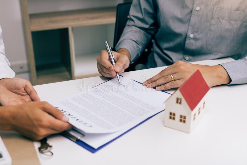 Os compradores de casa novos estão assinando um contrato de compra da casa na mesa do agente imagens de stock royalty free