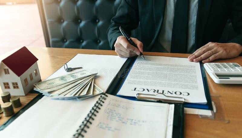 Os compradores de casa novos estão assinando um contrato de compra da casa na mesa do agente fotos de stock