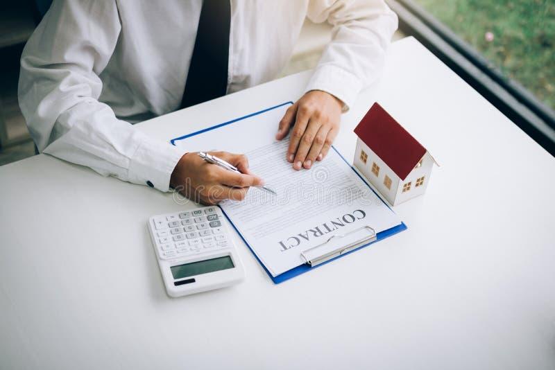 Os compradores de casa novos estão assinando um contrato de compra da casa na mesa do agente imagens de stock