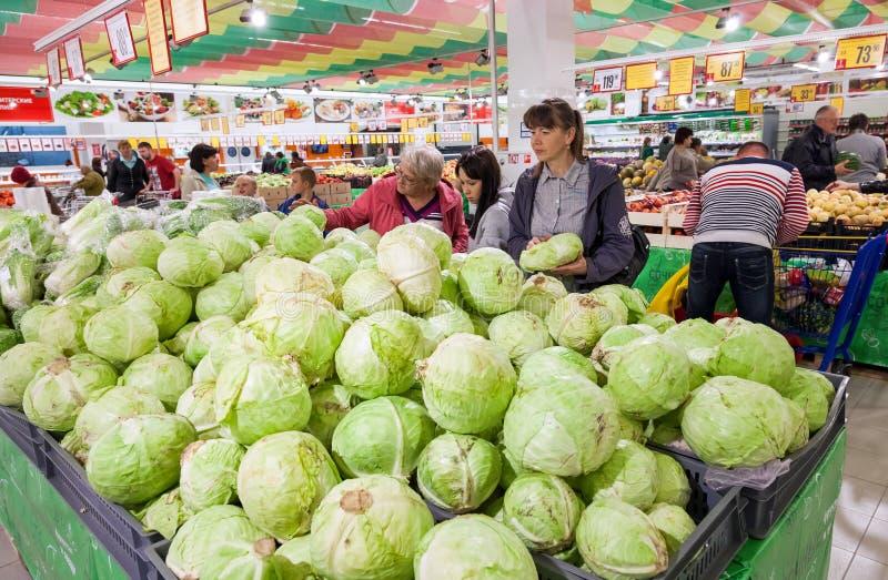 Os compradores selecionam legumes frescos no supermercado foto de stock royalty free