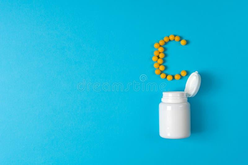 Os comprimidos amarelos em uma vitamina C derramaram de uma garrafa da medicina no fundo azul Comprimidos da medicamentação e da  fotografia de stock