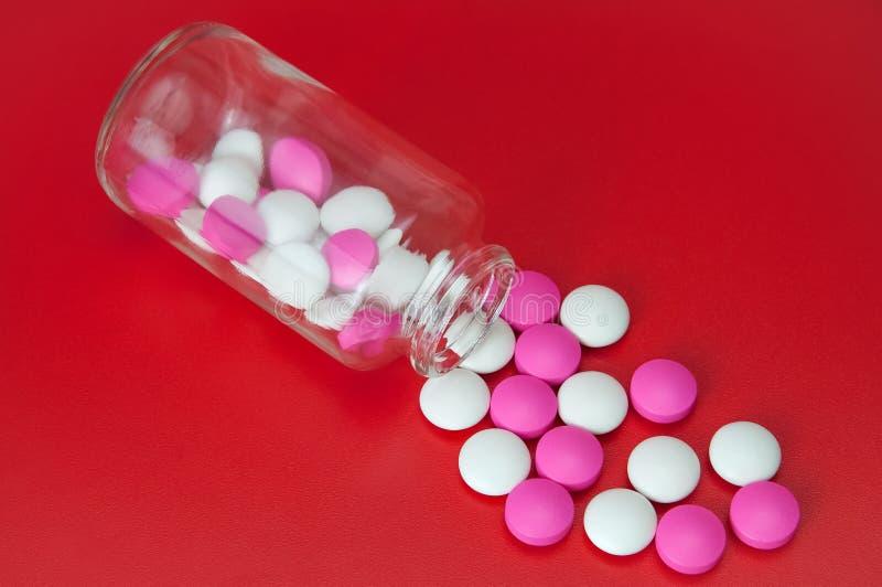 Os comprimidos cor-de-rosa e brancos dispersaram de um frasco de vidro em um fundo vermelho imagem de stock