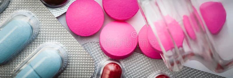 Os comprimidos cor-de-rosa são derramados de um frasco de vidro e as bolhas com tabuletas coloridas são dispersadas em um fundo b imagem de stock