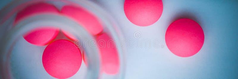 Os comprimidos cor-de-rosa são derramados de um frasco de vidro em um fundo azul branco A vista da parte superior imagem de stock