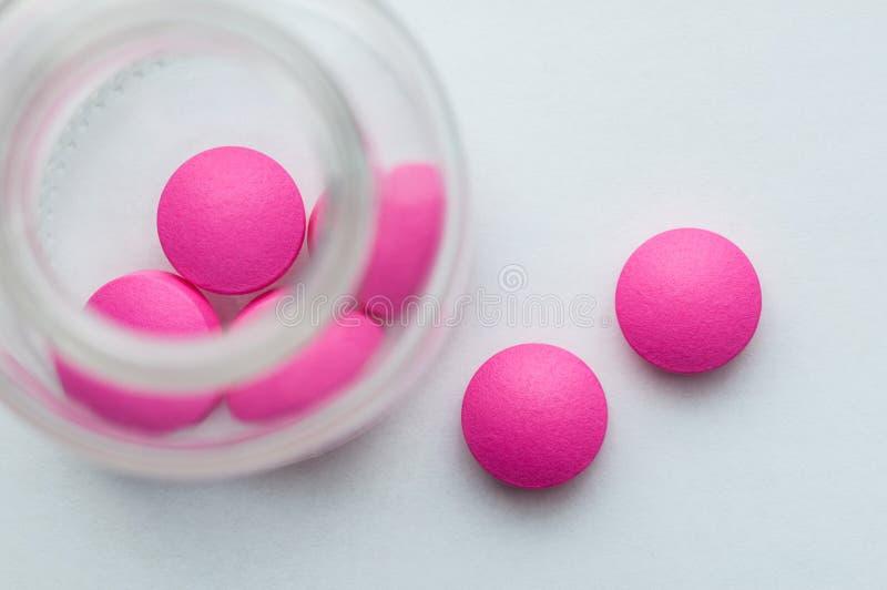 Os comprimidos cor-de-rosa são derramados de um frasco de vidro em um fundo branco A vista da parte superior imagem de stock royalty free