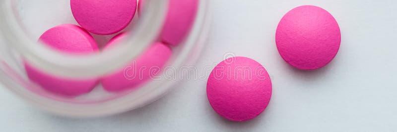 Os comprimidos cor-de-rosa são derramados de um frasco de vidro em um fundo branco A vista da parte superior fotos de stock