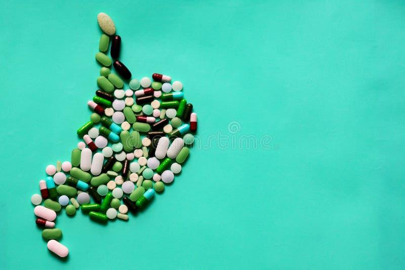 Os comprimidos da medicina marcam cápsulas na forma do estômago humano no fundo azul com espaço para o texto foto de stock royalty free