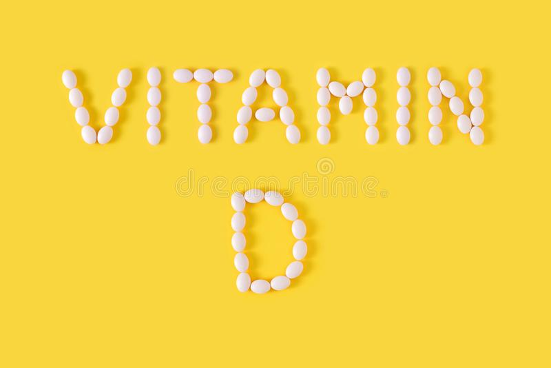 Os comprimidos da vitamina D deixaram cair da garrafa no fundo amarelo imagem de stock royalty free