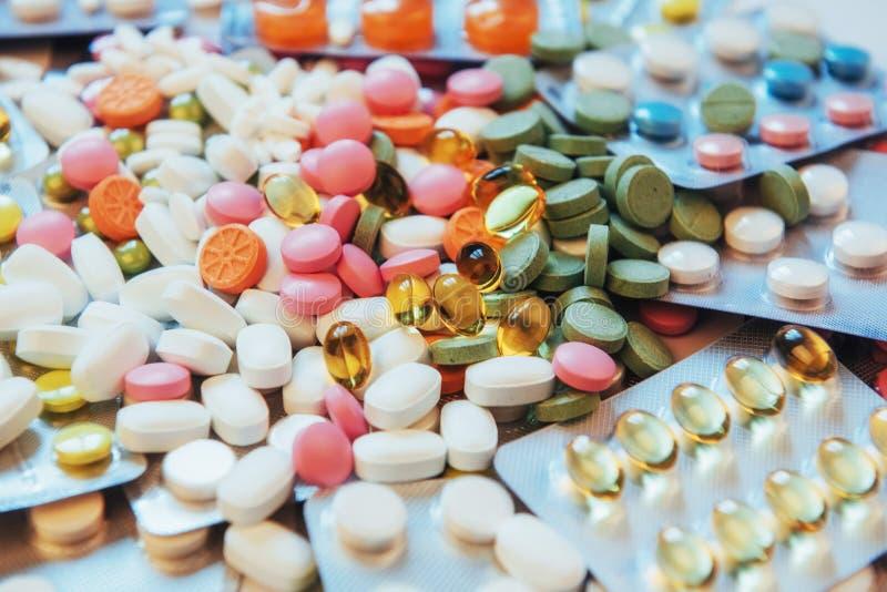 Os comprimidos de cores diferentes encontram-se na superfície em um pacote selado imagem de stock