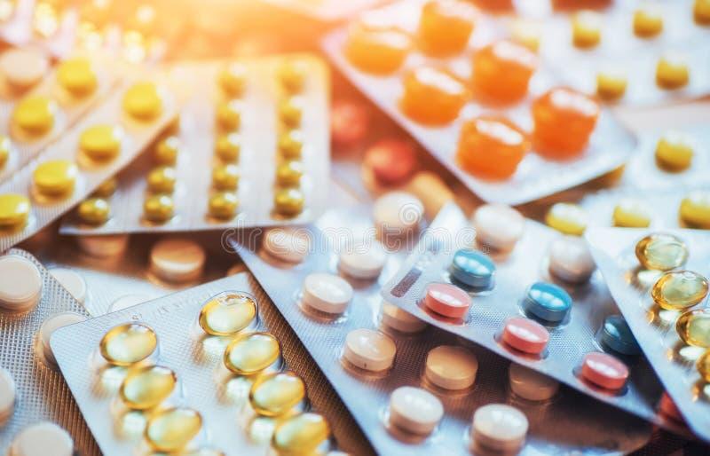 Os comprimidos de cores diferentes encontram-se na superfície em um pacote selado imagens de stock