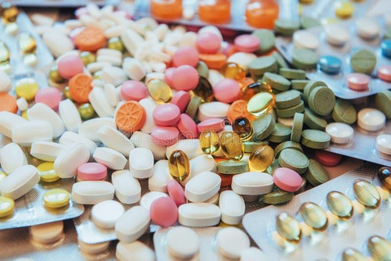 Os comprimidos de cores diferentes encontram-se na superfície em um pacote selado foto de stock