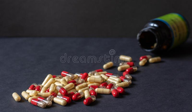 Os comprimidos derramaram para fora de um frasco em um fundo escuro fotografia de stock