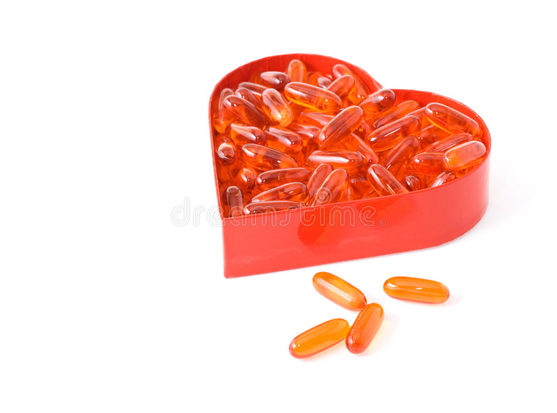 Os comprimidos do óleo de peixes no coração vermelho deram forma à caixa foto de stock royalty free