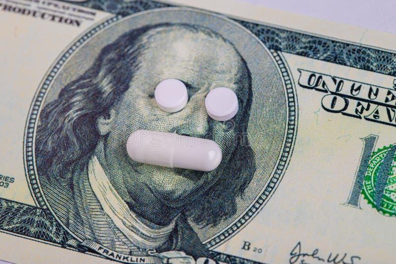 Os comprimidos encontram-se no lugar dos olhos, em uma conta de cem dólares de close-up O conceito da medicina do seguro, custo a imagem de stock royalty free