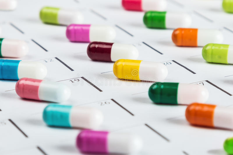 Os comprimidos são da cor diferente no calendário imagens de stock