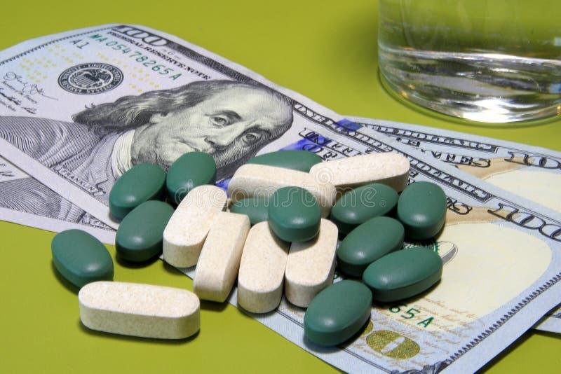 Os comprimidos verdes dispersaram em cem notas de dólar Custo do conceito saudável da vida imagem de stock