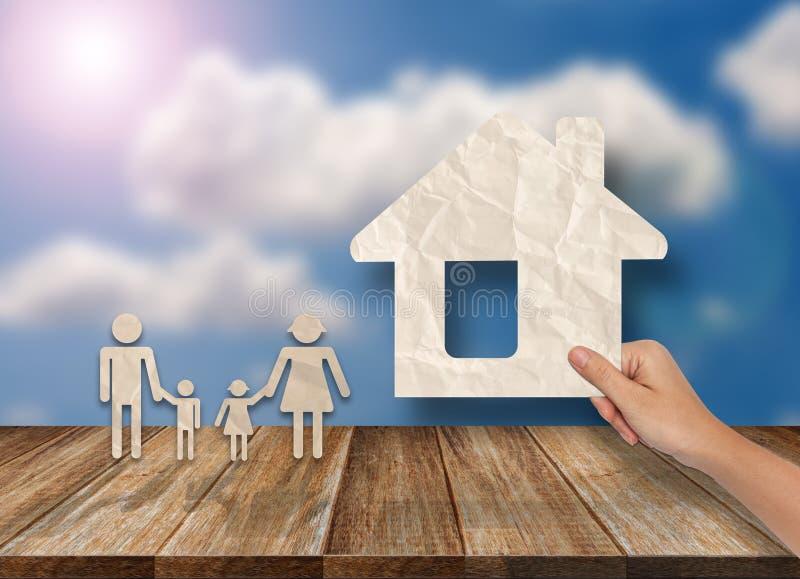 Os conceitos da mão puseram a casa e a família sobre a tabela de madeira imagem de stock royalty free