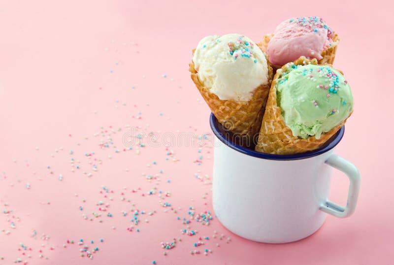 Os cones de gelado com polvilham no fundo cor-de-rosa fotografia de stock