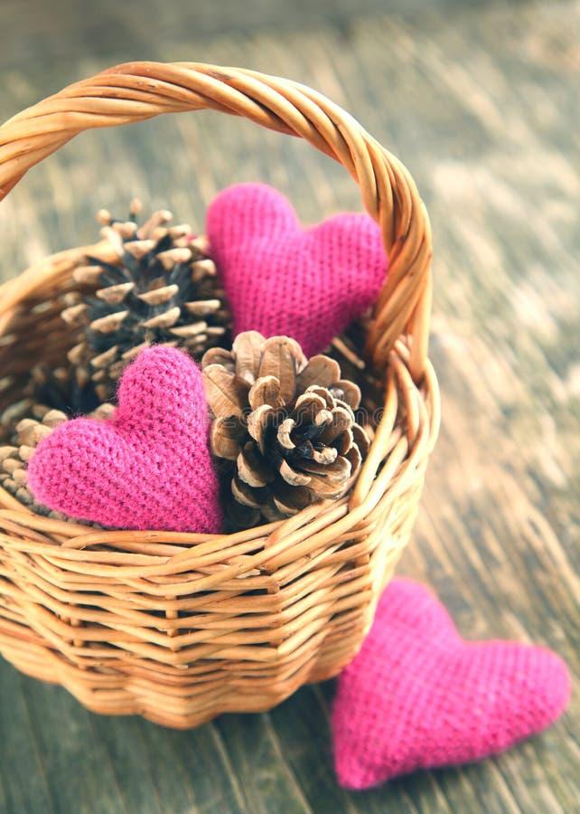 Os cones do pinho e feito a mão fazem crochê corações na cesta fotografia de stock royalty free