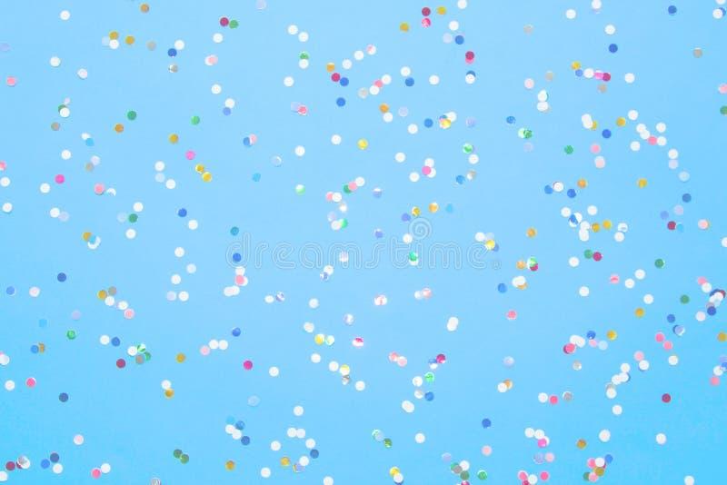 Os confetes coloridos dispersaram no papel azul Configura??o lisa foto de stock royalty free
