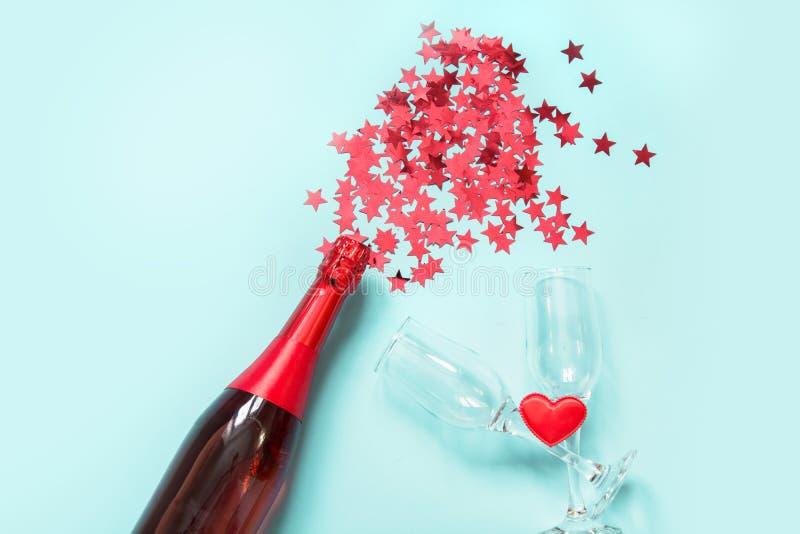 Os confetes na forma de estrelas vermelhas derramaram fora do champanhe da garrafa no fundo azul Vista superior foto de stock