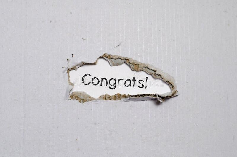 Os congrats da palavra que aparecem atrás do papel rasgado foto de stock